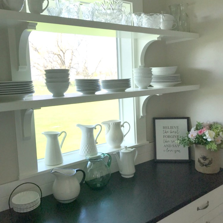 Open Shelving. It looks great in home decorating pictures. Is it practical? Here is our verdict after a year of use in our farmhouse style kitchen. Pros and Cons and pictures included. #openshelving #kitchendecor #whitekitchen #kitcheninspiration #farmhousekitchen